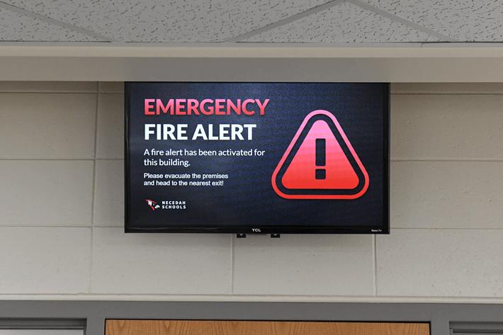 A digital sign showing an emergency alert message.