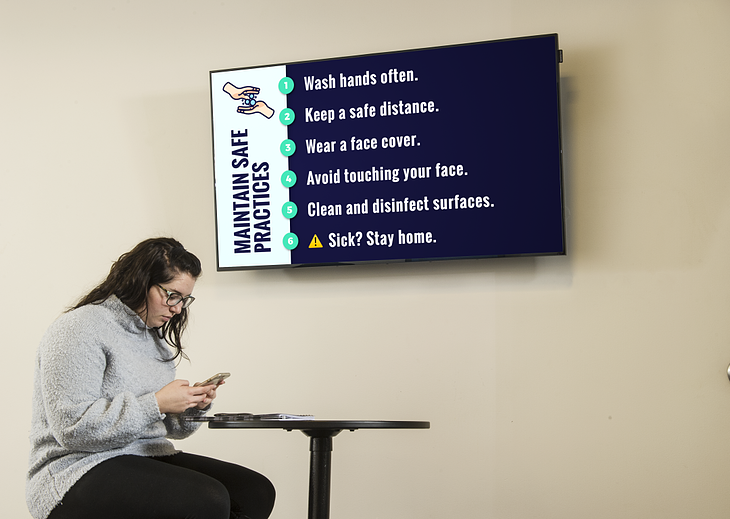 A girl sitting in front of a digital sign explaining safety best practices