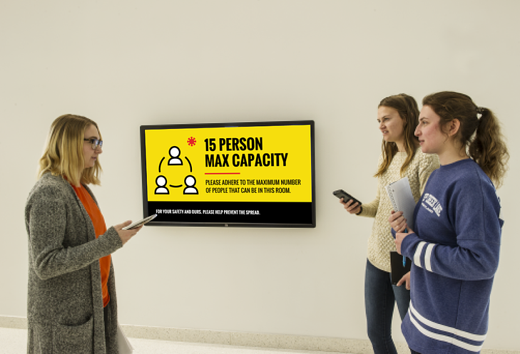 A group standing in front of a display explaining the maximum building occupancy