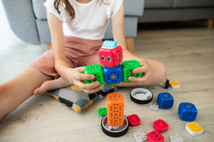 A girl in white shirt with stem activities blue and red car toy.