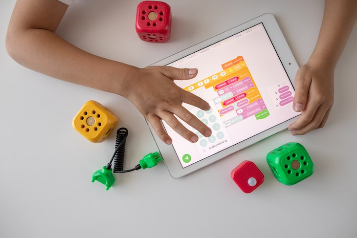 Person learning STEM holding a white ipad visual programming.