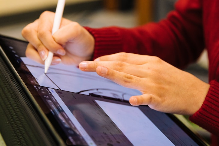 Student using interactive display and stylus.